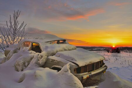 swept: Old car in the snowy wilderness at sunset. Choose the right machine in extreme climates Stock Photo