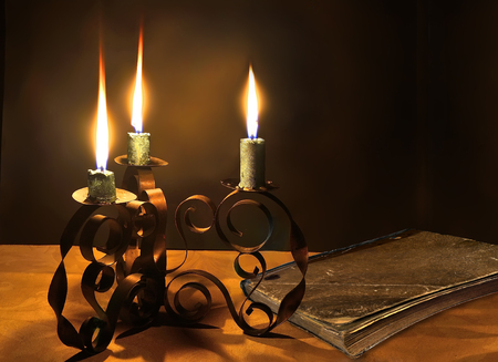 Closed old book in shabby cover and three burning candles in the coiled metal candlestick. Maybe its the bible or ancient lore, or history of someones love