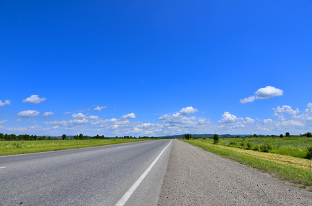 blue stripe: Straight empty road and roadside with cuttings grass running to horizon through meadows. Blue sky with white clouds and green hills on a background