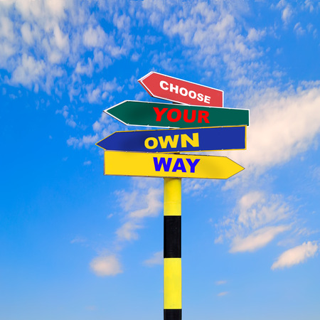 Sign post with four arrows of diffirent colors and directions and text - Choose your own way, on a blue sky background. Zdjęcie Seryjne