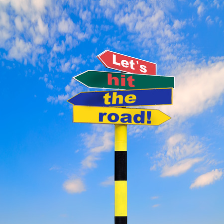 let s: Sign post with four arrows of diffirent colors and directions and text - Let s hit the road, on a blue sky background.