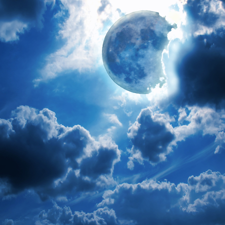 Full blue moon glowing among the fluffy clouds in the night sky - beautiful romantic background Stock Photo