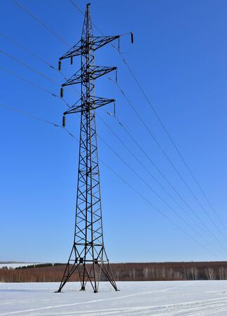 Tower and wires of high voltage power line on a winter landscape with blue sky