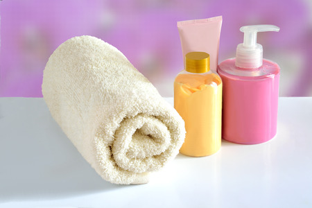 Natural hypoallergenic herbal Cosmetic products for skin care: plastic dispenser with liquid soap, bottle of lotion, tube of cream and white terry cotton towel on a pink floral blurred background Stock Photo