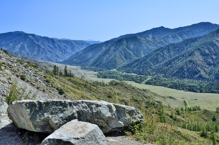 Beautiful summer mountains landscape, Altai, Russia. Mountain ridges covered with forest, a road through the valley and two large boulders at foreground