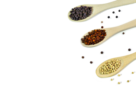 Black, red and white peppercorns in wooden spoons on a white background isolated. Natural spice and culinary flavor concept