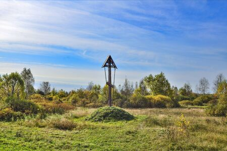 Alone  wooden cross by the road blesses passing travelers and reminds people who died in car accidents. Beautiful autumn landscape on a bright sunny September day Фото со стока