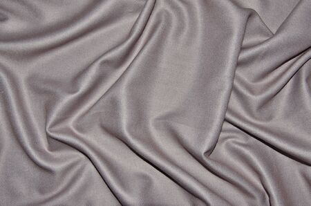 Top view of pale pink woolen with viscose fabric with soft folds - elegant textile background in trendy color. Female accessory - shiny silky scarf texture close up from natural fibers