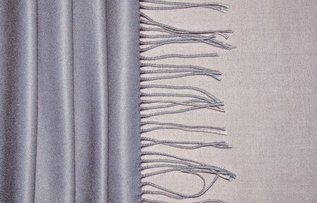 Luxury ladies gray-pink cashmere stole with fringe and soft drapery. Top view of woolen with viscose fabric with soft folds - elegant textile background in trendy colors. Female accessory Zdjęcie Seryjne
