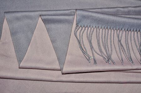 Luxury ladies gray-pink cashmere stole with fringe and soft drapery. Top view of  woolen with viscose fabric with soft folds - elegant textile background in trendy colors. Female accessory