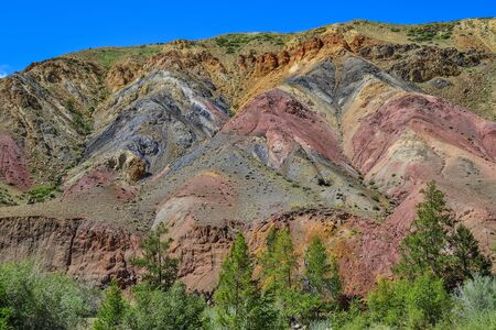 Texture of unrealy beautiful colorful clay cliffs in Kyzyl-Chin (Kisil-Chin) valley, Altai mountains, Russia. Summer landscape, which is called Martian for its fantastic unusual multicolored beauty Zdjęcie Seryjne