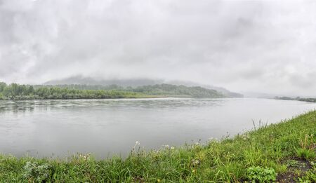 White fog over the forest on hill and river in summer morning - panoramic view. Moody landscape on the riverside. Green grass with drops of dew. Freshness and calmness of nature