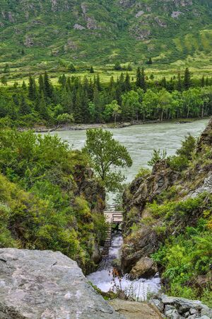 Wonderful nature of Altai mountains - gorge with Beltertuyuk waterfall, flowing into the Katun river. Beauty and purity of mountain nature, rapid stream falling from cliff. Travel concept