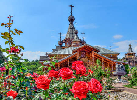 Novokuznetsk, Russia - July 29, 2019: Rose garden on front yard of Christian Temple of the Holy Martyr John the Warrior in Novokuznetsk, Russia. Bliss beauty of nature and wooden architecture of Russian North. Red roses in roses garden
