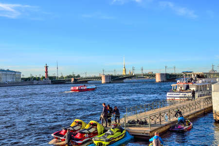 St. Petersburg, Russia - June 13, 2019: Boat trips and excursions for tourists on the Neva river by launch and jet skiing. Young guys on wharf are getting ready to ride scooters