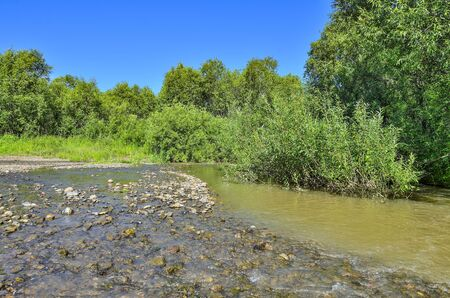 Idyllic summer sunny rural landscape on riverside. Shallow river with pebbles at the bottom and on the shore. Beauty and freshness of russian nature in summertime. Peaceful meditative mood scenery