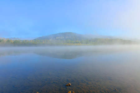 Early foggy morning over the river - beautiful summer landscape. Thick fog over the water surface, reflection of hill with forest covered on the bank - freshness, calmness and enjoyment of nature