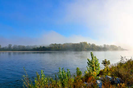 Early foggy morning over the river - beautiful summer landscape. Thick fog over the forest on the bank - freshness, calmness and enjoyment of nature