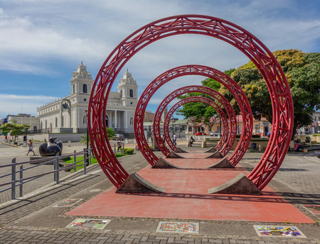 Sculpture of red rings in the middle of a square with a church in the background