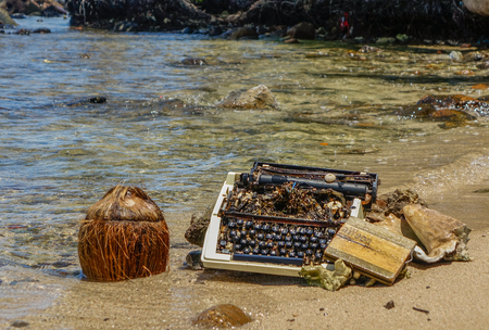 Old typewriter stranded on the shore of a paradisiacal beach