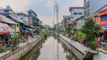 Narrow canal crossing the city of Bangkok, with small shops on the sides