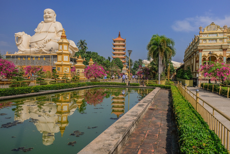 Huge statue of a white Buddha reflected in a pond of a Vietnam temple