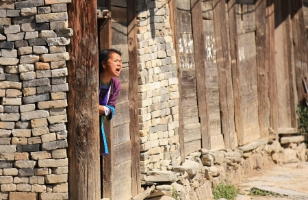 enmity: Woman of the Dong people at her home s door shouts loudly, apparently to nobody but seemingly in enmity with the whole village, repeatedly, entering the house and after a while getting out to shout again, time after time  Chongzhang, Guizhou, China
