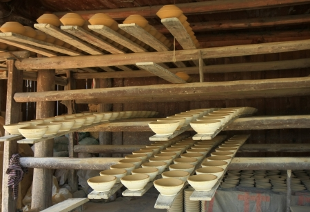 shelfs: Traditional pottery works of the Miao people set on wooden shelfs waiting for finishing in a mill beside the road on the Xijiang-Rongjiang route, Leishan county, Guizhou, China