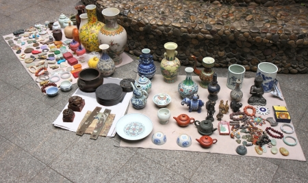 Antiques and second hand items for sale  ceramics and chinaware vases, figurines, jewellery, teapots, cups, stones, boxes   placed on the floor in a courtyard of downtown Kunming, Yunnan, China  Stock Photo - 14376530