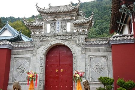 splendour: Garnet coloured door flanked by lion and elephant sculptures, in a grey stone wall topped by roof shaped decoration in the Huating-Pavilion of Splendour buddhist temple, Xishan-Mountains of the West area over the Dian Chi-Lake Dian, Kunming, Yunnan, China