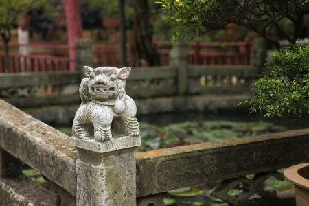 occupying: Lion shaped sculpture placed in a corner of the banisters sorrounding a pond occupying the centre of a courtyard in the Huating-Pavilion of Splendour buddhist temple, Xishan-Mountains of the West area facing the Dian Chi-Lake Dian, Kunming, Yunnan, China