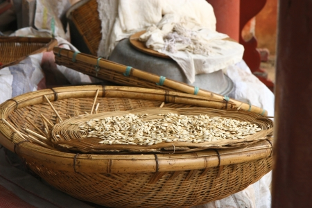 splendour: Handicrafted wicker basket with pumpkin seeds along with othe wicker items, white cloths laid on a table in a porch of the Huating-Pavilion of Splendour buddhist temple, Xishan-Mountains of the West area, over the Dian Chi-Lake Dian, Kunming-Yunnan, China Stock Photo