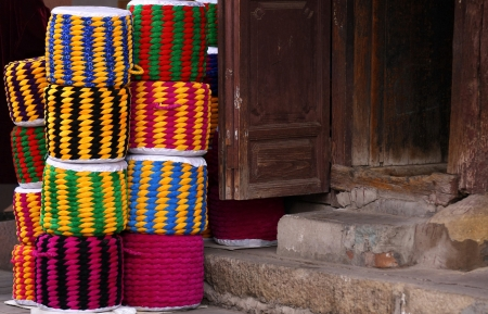 artisanal: Handmade, colourist, traditional, artisanal, braid cloth made cylindrical seats, piled on the pavement at a house s door in a street of the old town Weishan, Yunnan, China