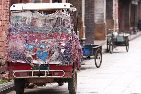matiere plastique: Vieux tricycle � moteur chinois avec une couverture tout fissur� mati�re plastique, stationn� dans une rue de la vieille ville Weishan, Yunnan, Chine