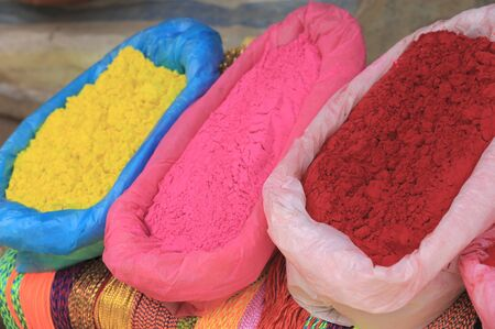 hinduist: Plastic bags containing colored powders, yellow pink and red, placed over manycolored strings at the exit of the Dakshin Kali hinduist temple, Pharping, Kathmandu, Nepal