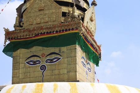 The eyes of the Buddha on the west looking face of the tower over the stupa, with the nepali symbol for unity among them, Swayambhunath, Kathmandu, Nepal