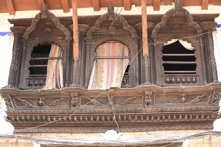 traditional house: Carved wooden triple window on a traditional house wall with flowery cloth curtains in the old town Patan-Lalitpur District-Nepal