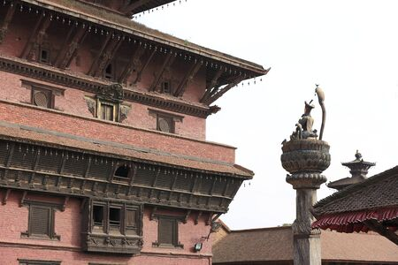 Bronze statue of King Yoganarendra Malla under cobra snake-flanked by his wifes-over stone column facing the Royal Palace  In the Durbar Square of Patan-Lalitpur District-Nepal  Editorial