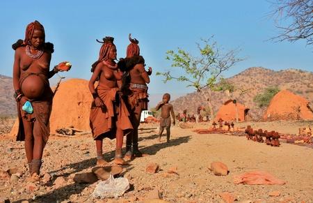 atender: Epupa, KAOKOLAND  NAMIBIA - 16 DE OCTUBRE: Himba mujeres-una embarazada asistir a sus puestos de Souvernir el 16 de octubre de 2010 en una aldea cerca de Epupa estacional, Kunene, Namibia, Kaokoland. Girl-nombre del ni�o en edad: Hikuminwe-4. Editorial