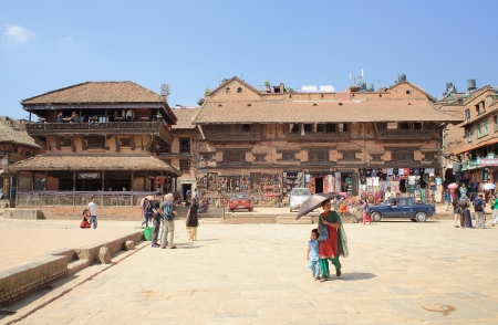 BHAKTAPUR, NEPAL - OCTOBER 5: Photo seeking tourists merge with orange dressed sadhu and locals going to their tasks while they traverse the Taumadhi Tole Square on October 5, 2012 in Bhaktapur-Kathmandu Valley-Nepal.