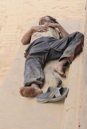 workingman: BHAKTAPUR, NEPAL - OCTOBER 5: Nepali workingman sleeps at noon-siesta after having worked the whole morning on October 5, 2012 in the Durbar Square of Bhaktapur-Kathmandu Valley-Nepal.