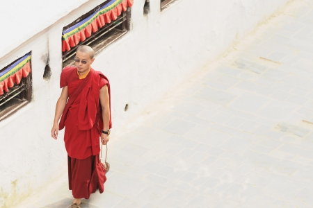 BOUDHANATH, KATHMANDU, NEPAL - OCTOBER 5  Tibetan lama-priest follows the pathway around the Boudhanath stupa as a prayer to the Buddha on October 5, 2012 in Kathmandu-Nepal  Editorial