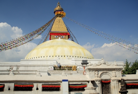 The great stupa of Boudhanath-Bodhnath with buddhist prayer flags hanging from its pyramidal tower and the eyes of the Buddha looking towards the 4 cardinal points  Kathmandu-Nepal