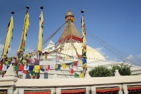 The white big stupa of Boudhanath-Bodhnath with many colored buddhist prayer flags hanging from its golden 13 storey tower-the eyes of the Buddha looking towards the 4 cardinal points-sorrounded by prayer wheels  Kathmandu-Nepal