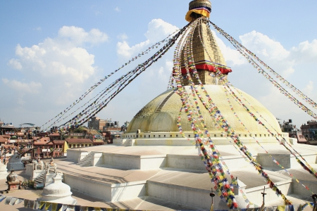 The great white stupa of Boudhanath-Bodhnath showing the eyes of the Buddha lookin at the 4 cardinal points and many colored buddhist prayer flags hanging from its 13 storey golden tower  Kathmandu-Nepal