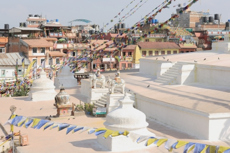 Platforms supporting the stupa of Boudhanath-Bodhnath and the buildings surround it  Buddhist prayer flags hanging from the top  Kathmandu-Nepal