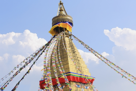 Many colored buddhist prayer flags hanging from the 13 storey pyramidal golden tower crowning the great white stupa of Boudhanath-Bodhnath with the eyes of the Buddha looking at the 4 cardinal points  Kathmandu-Nepal