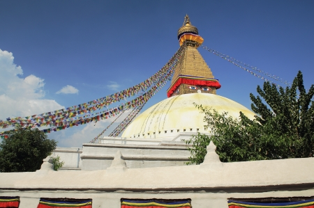 The white great stupa of Boudhanath-Bodhnath with buddhist prayer flags hanging from its pyramidal tower and the eyes of the Buddha looking towards the 4 cardinal points  Kathmandu-Nepal