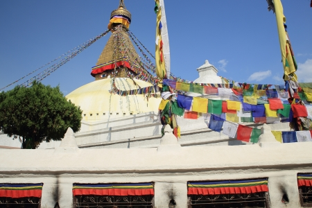 The great white stupa of Boudhanath-Bodhnath with many colored buddhist prayer flags hanging from its 13 storey pyramidal golden tower-the eyes of the Buddha looking towards the 4 cardinal points-sorrounded by prayer wheels  Kathmandu-Nepal  Imagens