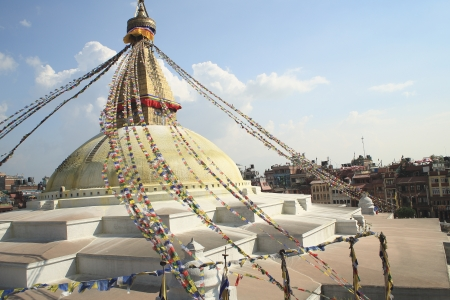 Many colored buddhist prayer flags hang from the 13 storey golden tower crowning the great white stupa of Boudhanath-Bodhnath with the eyes of the Buddha looking towards the 4 cardinal points  Kathmandu-Nepal